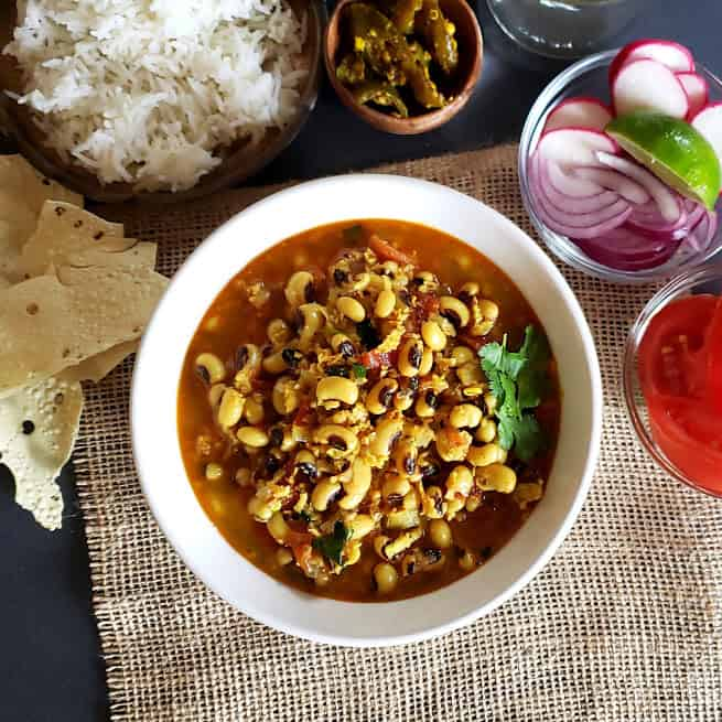 A dinner serving of creamy black-eyed peas and coconut curry with rice, pickle, papad and fresh onion tomato salad.