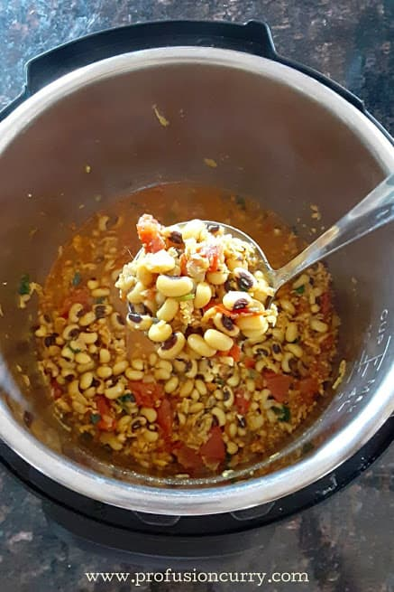 A ladle full of cooked black eyed peas with spices. These beans are cooked in Instantpot.