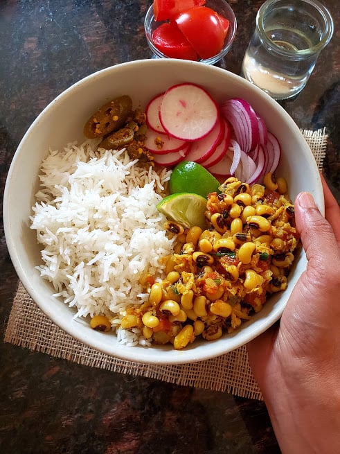 A hand holding a bowl full of rice, raddishes, pickle and curry.