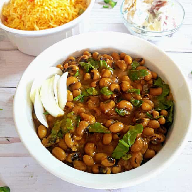 Black Eyed Peas cooked with onions, tomatoes and spinach with delicious seasoning served in white bowl.