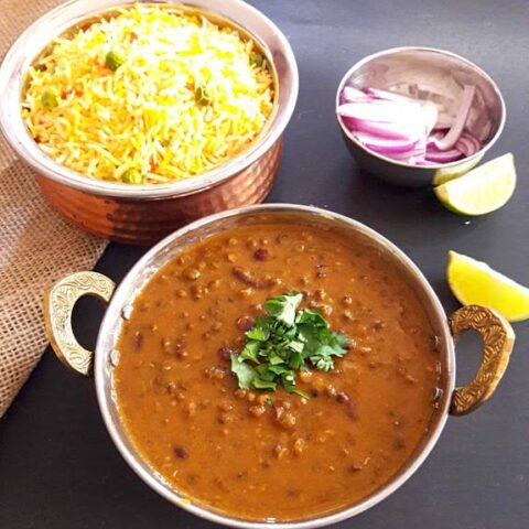 Dal Makhani garnished with cilantro leaves served in copper bowl. A bowl of lemon rice and a bowl of cut red onion and lemons in the background.