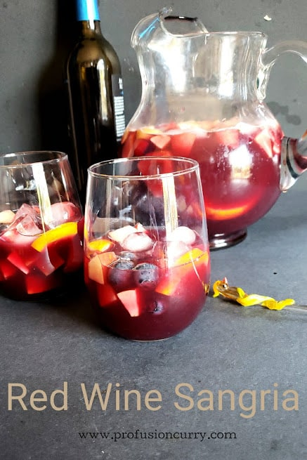 Two glasses full of diced fruit, ice and fruity sangria.