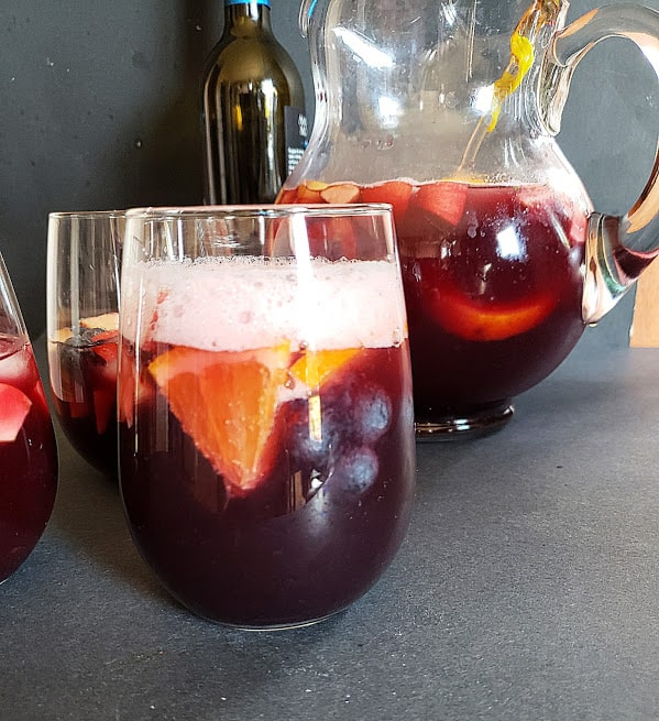 An ice cold and fizzy red wine sangria served in a wine glass.