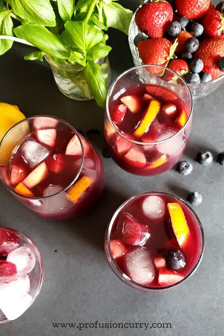 overhead shot of glasses filled with ice cold red wine and fruit drink.