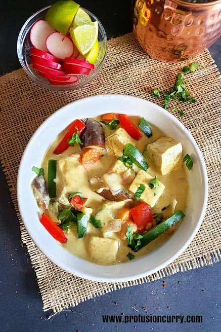 A white serving bowl full of tofu, vegetables in creamy coconut curry.