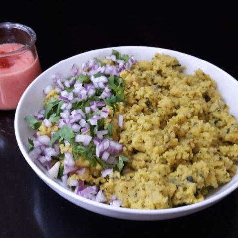 A serving bowl filled with Moong Daal Khichadi served garnished with chopped onions and cilantro.