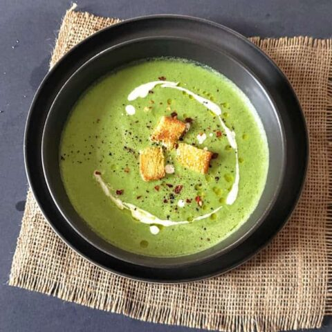 A soup bowl filled with creamy asparagus broccoli soup garnished with olive oil, light cream and croutons.