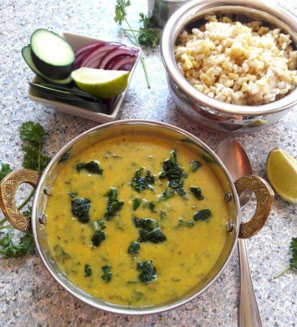 Spinach Lentil Curry with onions, lime wedges and rice