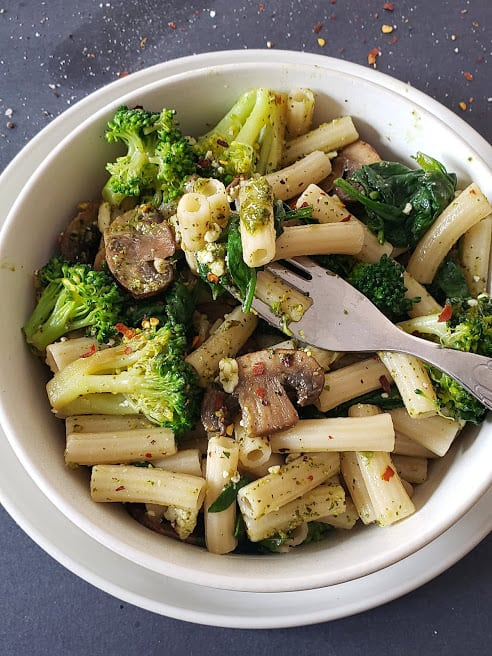 A fork holding some sauce coated pasta and cooked vegetables.