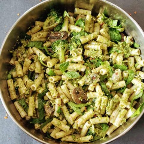 A skillet full of pesto coated vegetables and pasta to make this Penne Pesto Primavera recipe at home.