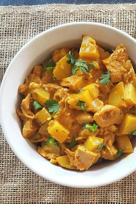 A white bowl full of turmeric jackfruit curry made in Instant Pot.