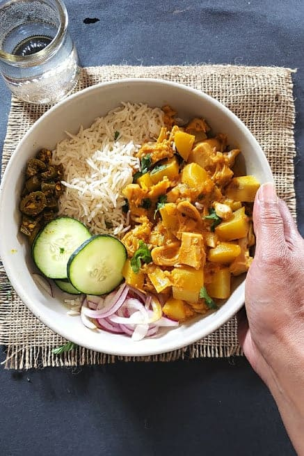 A hand holding a bowl of rice, curry, pickle and salad dinner.