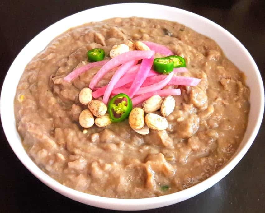 Pinto Beans served as mexican style refried beans in white bowl and garnished with pickled onion and jalapeno pepper slices
