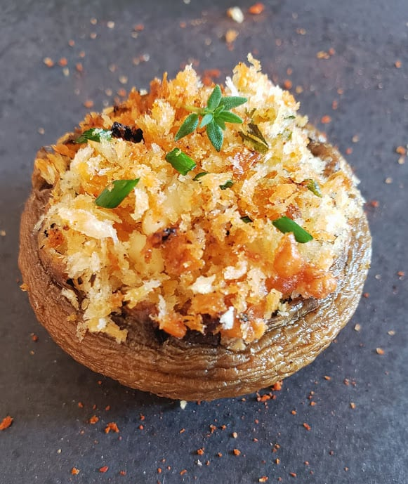 A close up image of baked mushroom stuffed with bread crumbs, italian seasoning, cheese and minced garlic.