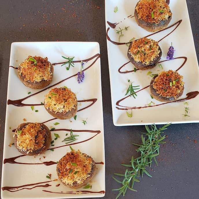 Stuffed mushrooms arranged on two serving platters decorated with herbs and flowers.