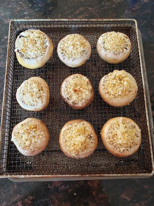 Freshly stuffed mushroom caps arranged on air fryer basket.