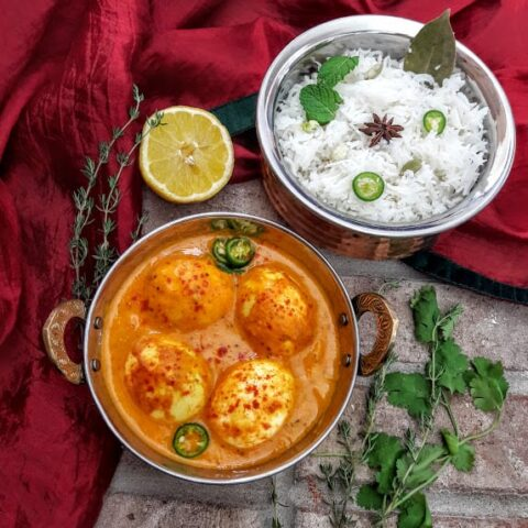 An over head shot of Indian Egg curry and white rice served in copper containers.