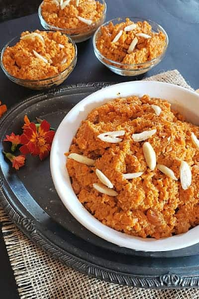 Gajar Halwa served in three glass bowls and large serving container.