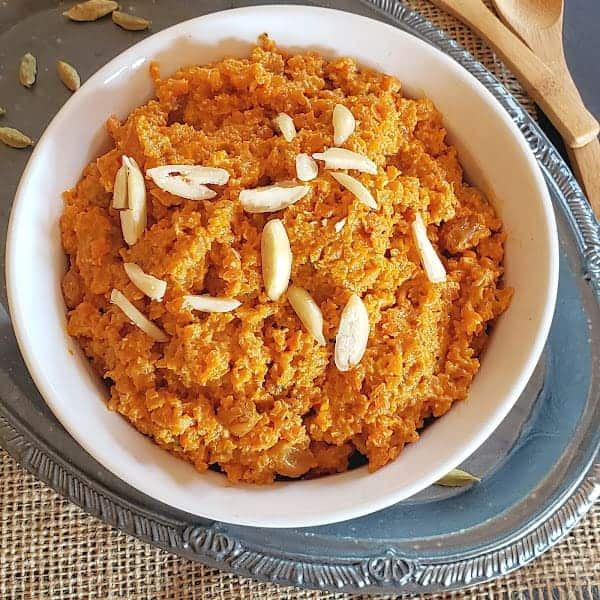 Carrot Almond Pudding is a traditional Indian dessert called Gajar Halwa. It is served in a white bowl with almond garnish.