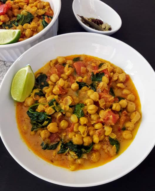 Close up of a bowl full of curried chickpeas, and spinach and crushed tomatoes.