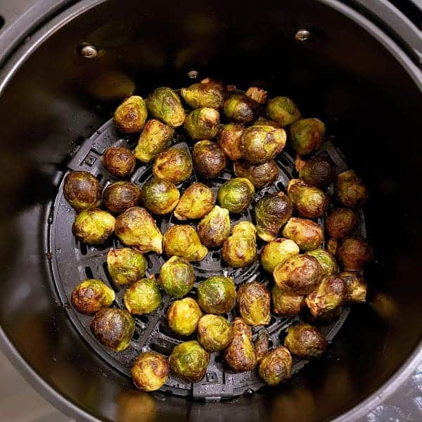 Charred Brussels Sprouts in the air fryer basket.