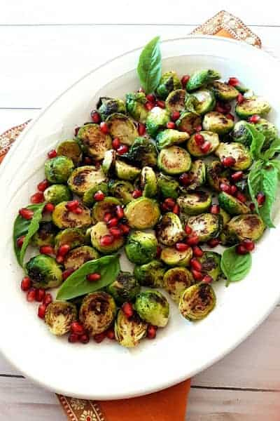 An overhead shot of serving platter full of roasted Brussels Sprouts with garnishes.