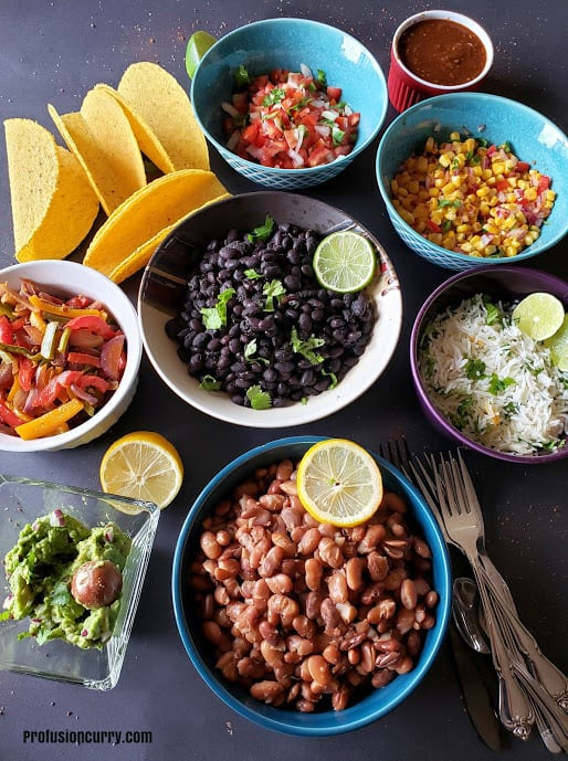 Colorful bowls full of beans, rice and condiments set up for make your own taco bar.