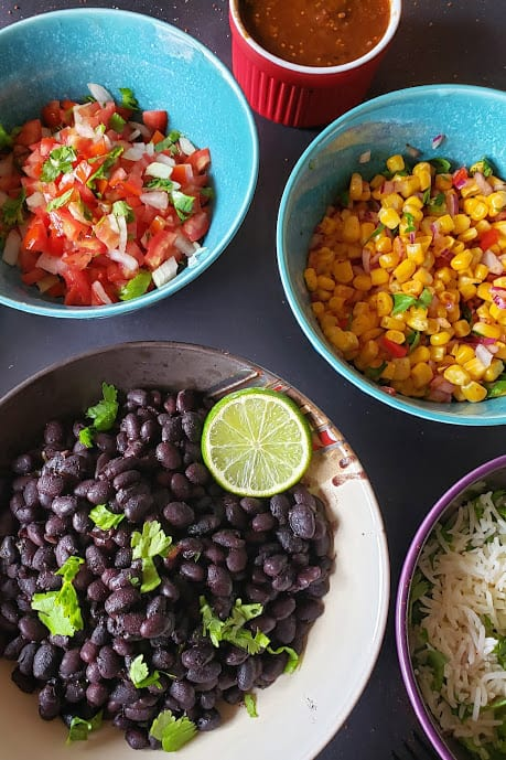 Close up of the bowls full of cuban black beans, corn and salsa.