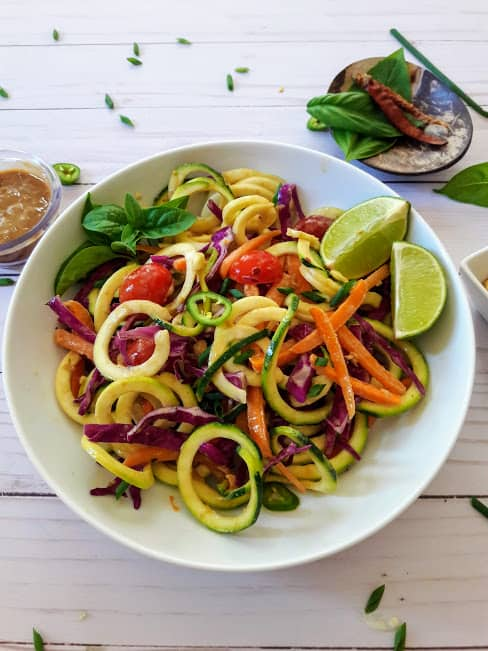 A white dinner plate full of colorful vegetable noodles.
