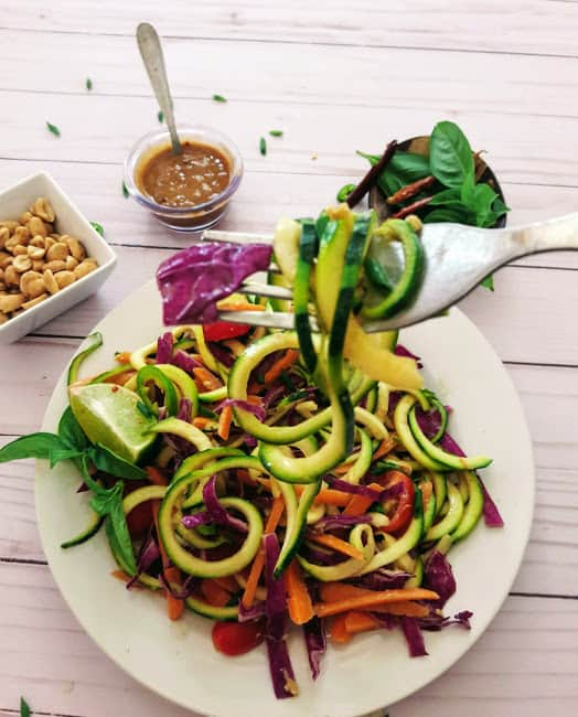 A fork holding spiralized vegetables used in Thai Zucchini Noodles recipe.