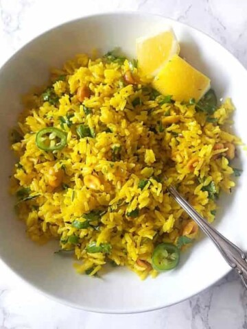 Turmeric Lemon rice served in a white bowl along with lemon wedges and chopped cilantro and green pepper.