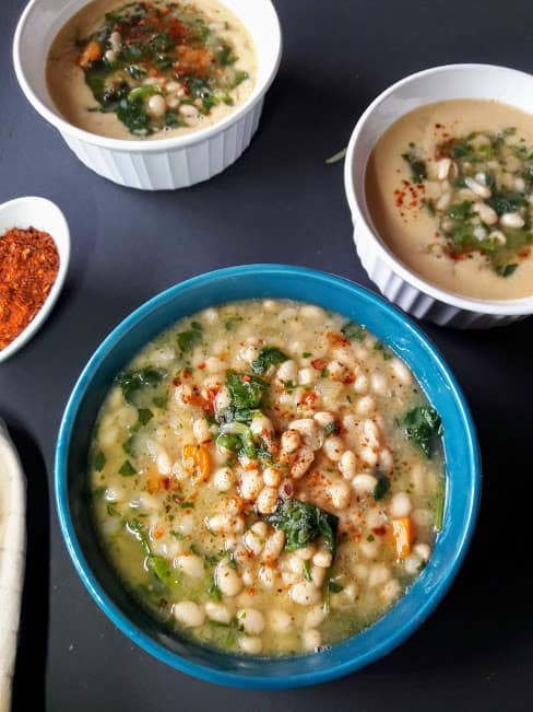 A dinner serving of white bean spinach soup in three soup bowls.