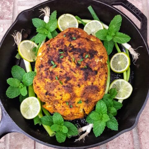 Whole Roasted Cauliflower served on black cast iron skillet with mint, lemon wedges and green onion garnish.