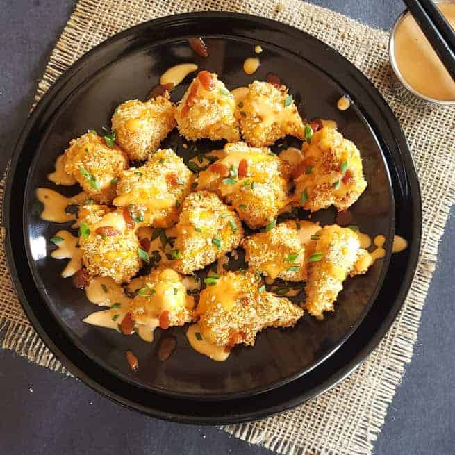 Crispy non fried cauliflower bites tossed with spicy, creamy bang bang sauce served on a black dinner plate.