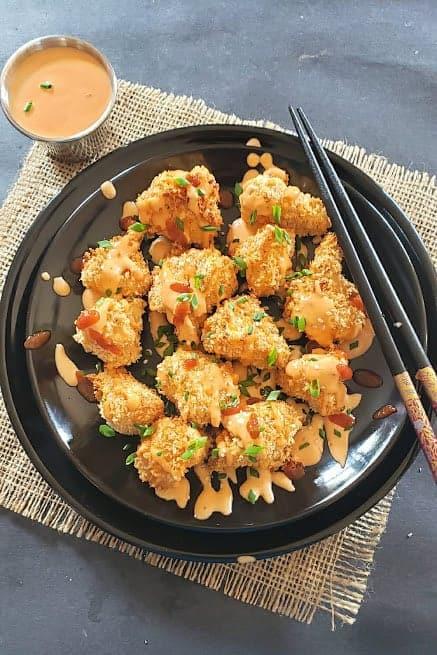 Crispy Cauliflower bites served with sauce and chopsticks.