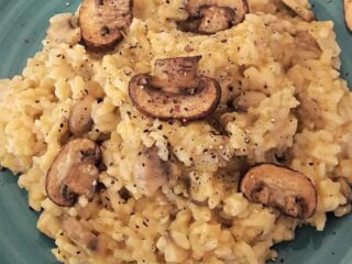 Homemade vegan Mushroom Risotto with creamy texture served with sautéed mushrooms on top.