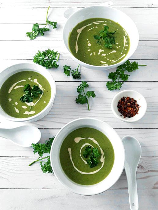 Green Pea and Mint Soup in 3 serving bowls with decorations