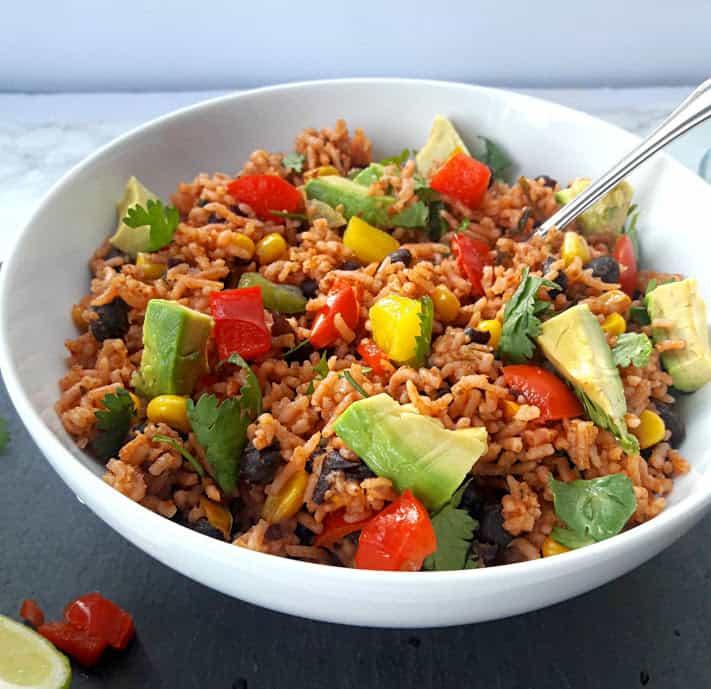 Encilada Rice Bowl with cilantro and avacado slices as garnish with a spoon