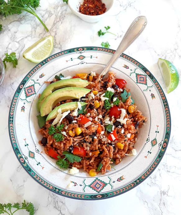 Vegan enchilada rice with garnishes and lime wedges overhead shot