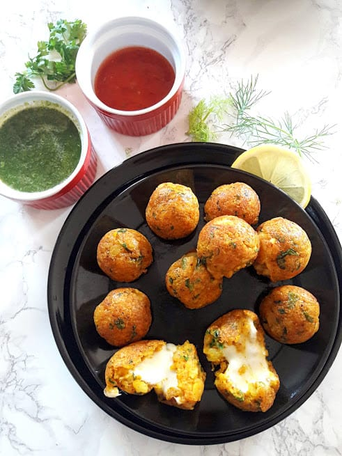 Cheesy Potato Poppers with lemon wedge and chili and cilantro sauce