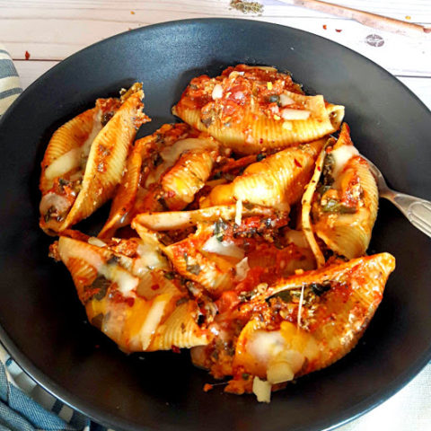 Instant Pot created Stuffed Pasta Shells with spinach, cheese and Italian Seasoning. Pefect weeknight comforting dinner served on black plate with cheese sprinkled on top.