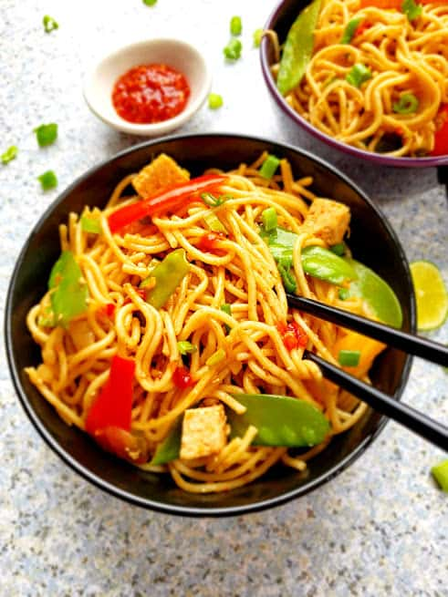 Chili Garlic Asian Noodes with snow peas, sweet red pepper strips and marinated tofu on black serving bowl. This delicious recipe by ProfusionCurry is easy and healthy.