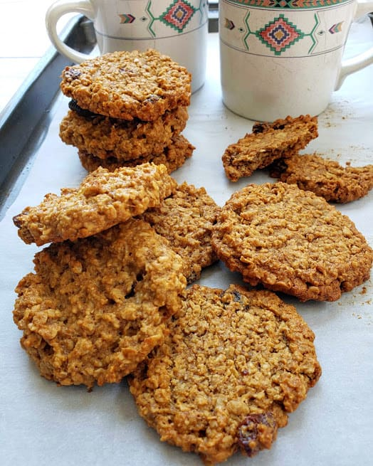 freshly baked Vegan and Glutenfree Banana Oatmeal rasin cookies served on tray with two coffee cups in the background