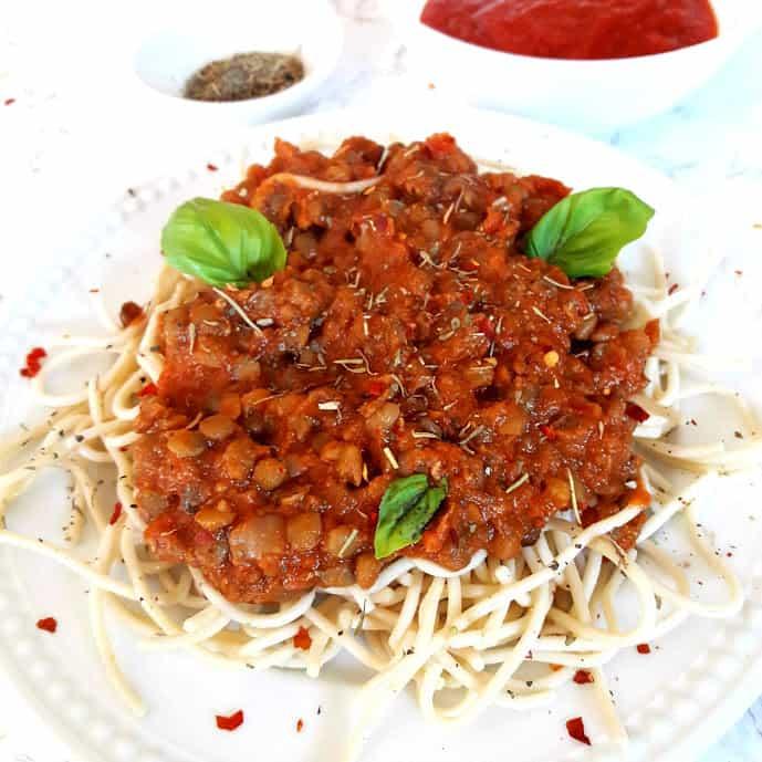 Spaghetti Lentil Bologneseserved with fresh basil leaves in a white dinner plate.