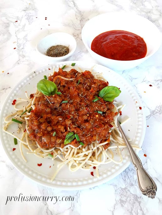 Close up photo of lentil bolognese sauce served over gluten free spaghetti. The dinner is served in white dinner plate with fresh basil leaves and red chili flakes garnish.