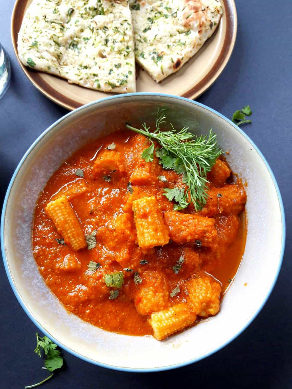 Baby Corn Masala served with cilantro and fenugreek leaves along with garlic naan.