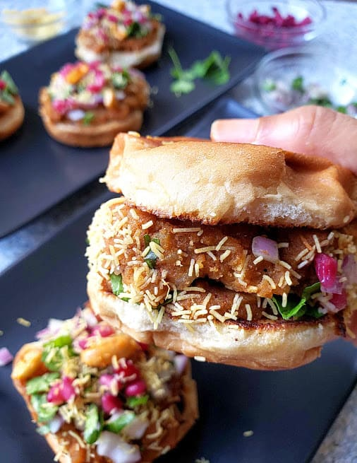 Close up shot of prepared Dabeli, Indian version of potato slider showing layers of garnishes and texture.