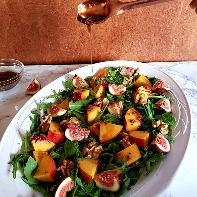 maple vinegratte in copper spoon getting drizzled on Fig Arugula Salad
