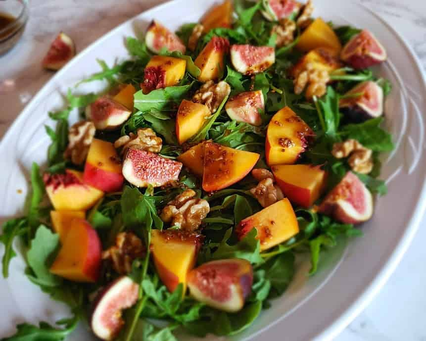 Close up view of tossed up fig arugula salad