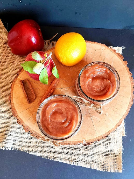 overhead photo shot of homemade apple butter sauce showing caramel colored thick apple butter in two glass container along with few fresh apples and a lemon.